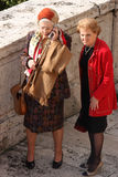 Elderly modern. Two aged ladies are walking in the historic center of Rome / one of them has a conversation using his smathphone / Groomed and elegant clothes / royalty free stock photo
