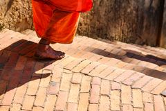 Buddhism Monk walks down the stairway. An elderly monk makes his rounds in very older temples, Kathmandu, Nepal Royalty Free Stock Images
