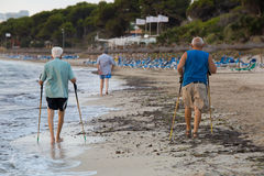 Elderly morning walk. Majorca, Spain - July 28, 2015: Elderly people having their early morning walk on the beach near Alcudia on the Balearic island of Majorca Royalty Free Stock Image