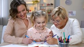 Elderly mother, daughter and grandchild drawing by color pencils, time together. Stock photo royalty free stock image
