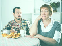 Elderly mother resents her son. Son defends his position before adult mother at home Royalty Free Stock Image