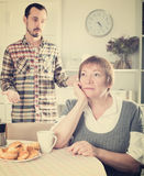 Elderly mother resents her son. Son defends his position before adult mother at home Stock Photos