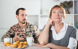 Elderly mother resents her son. Mature mother was angry at her son and offended him at home Stock Photos