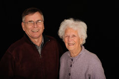 Elderly mother and son. Half body portrait of smiling elderly mother and son, isolated on black background Stock Photo