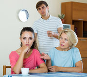 Elderly mother and young man blaming girl in something. Offended young women listening to rebukes from mother and husband Stock Photos