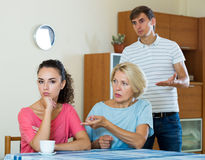 Elderly mother and young man blaming girl in something. Offended young women listening to rebukes from mother and husband Stock Photography