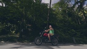 Elderly motorcyclist driving on motorbike on countryside road on tropical palm trees landscape. Senior man riding.  stock video
