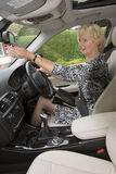 Elderly motorist adjusting rear view mirror in a car Royalty Free Stock Photos