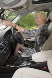 Elderly motorist adjusting rear view mirror in a car Royalty Free Stock Photos