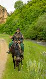 An elderly mountain dweller on horseback. An elderly resident of the North Caucasus in a mountain ravine near river Stock Images