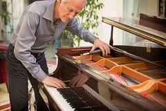 Elderly music instrument technician tuning a piano keyboard. Elderly music instrument technician tuning piano keyboard with tuning spanner. Musician checking royalty free stock photography