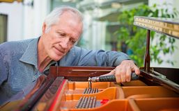 Elderly music instrument technician tuning a piano keyboard. Elderly music instrument technician tuning piano keyboard with tuning spanner. Musician checking stock image