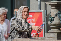 Elderly muslim woman fill bottle drink water from drinking fount Royalty Free Stock Photos