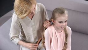 Elderly nanny combing little girl hair, preparing to party primary school, care. Stock photo royalty free stock photography