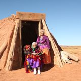 Elderly Native American Women. Pose outside a tribal abode. They are full length viewable and looking at the camera. Squarely framed shot Stock Photography