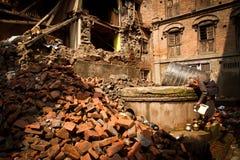 A elderly Nepali lady uses a well amongst the earthquake ruins i Stock Image
