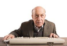 Elderly nerd. Work with his vintage keyboard Royalty Free Stock Image