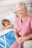 Elderly nurse in USA pediatrics with child patient Royalty Free Stock Images