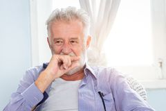 Elderly old man cute hiding smile look shy. Sitting in room with window stock photo