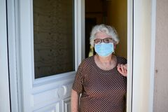 Elderly old senior woman opening front door of house and welcoming people at home wearing a surgical mask to avoid covid19 and cor