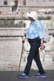 Elderly old turist woman walking with stick in Rome (Italy). An elderly tourist is walking with his stick on the Ponte Vittorio Emanuele in Rome (Italy). Behind Stock Image