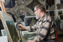 Elderly painter with beard and glasses draws a flowers picture by oil paint in art workshop Stock Image
