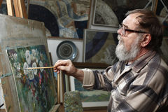 Elderly painter with beard and glasses draws a flowers picture by oil paint in art workshop Stock Photos