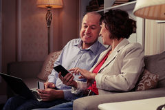 Elderly pair sitting indoors and communicating with one another Royalty Free Stock Photos