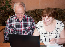 Elderly pair at the table with a notebook Royalty Free Stock Photos