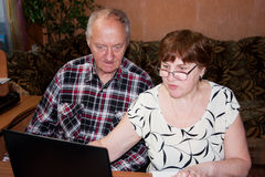 Elderly pair at the table with a notebook Royalty Free Stock Image