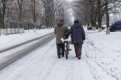 Elderly pair walking on a winter street rolling old bicycle loaded with bags in Dnepr city, Ukraine Stock Images
