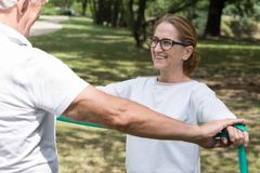 Elderly pair workout with band. Picture of elderly pair workout with fitness elastic band stock photo
