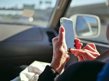 Elderly passenger in car looking at smart phone on the road for navigation while driving. royalty free stock photography