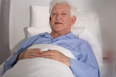Elderly patient in bed. Seriously ill elderly patient lying in hospital bed Stock Image