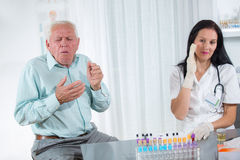 Elderly patient coughs into the doctor's office Stock Photo