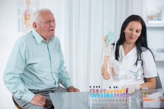 Elderly patient coughs into the doctor's office Royalty Free Stock Photo