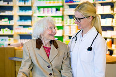 Elderly patient happy with her smiling doctor. Elderly happy female patient next to smiling doctor with pony tail and eyeglasses standing in front of pharmacy Royalty Free Stock Photo