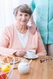 Elderly patient with indigestion problem. Picture of elderly patient with indigestion problem drinking tisane Stock Image