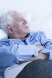 Elderly patient lying in hospital bed Stock Images