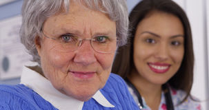 Elderly patient and Mexican caregiver looking at camera stock images