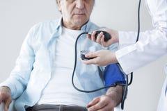 Elderly patient and nurse is measuring impulse royalty free stock photo