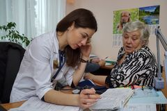 Elderly patient at a nurse`s appointment. Doctor in the clinic is studying medical examinations of an elderly patient.nPensioner taking care of health came to Stock Images