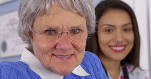 Elderly patient smiling with Mexican caregiver. Cheerful elderly patient smiling with Mexican caregiver Stock Photos