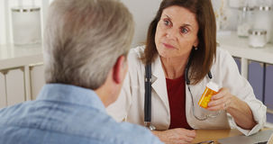 Elderly patient talking doctor about prescription in office Royalty Free Stock Photos