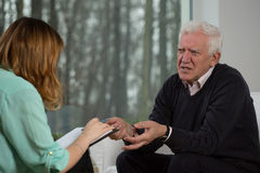 Elderly patient talking with psychotherapist Royalty Free Stock Image