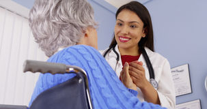 Elderly patient thanking Mexican woman doctor. Senior patient thanking Mexican women doctor Royalty Free Stock Photography