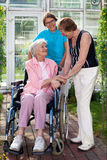 Elderly Patient on Wheel Chair with Two Caregivers. Royalty Free Stock Image