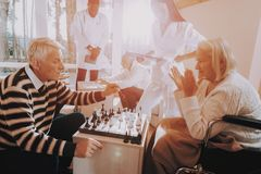 Elderly. Patient on a Wheelchair. Chess Play. Happy old family time together. Aged men play with old woman. game with family. Old wife with young nurse. Love royalty free stock image