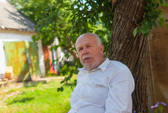 Elderly peasant sitting under tree shadow at summer season Stock Image