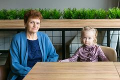 Grandmother and granddaughter sit at a table in a cafe. stock photo